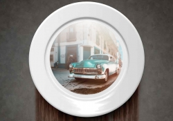 A plate, mounted to a slate gray wall, with the image of a vintage car in the center. The wall beneath the plate is discolored.