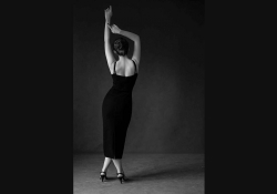 A black and white photograph of a woman dancing, her back turned to the viewer