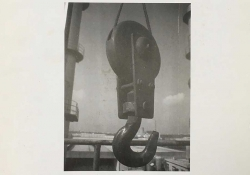 A grainy black and white photograph of a huge industrial crane hook suspended mid-air