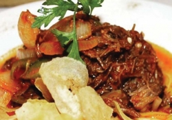 A portion of stewed meat, garnished with parsley, served with a small bed of chips