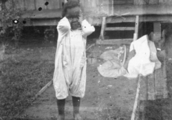 A double exposed black and white photograph of a young African American child with a women seated perpendicular to the main image