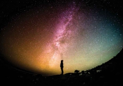 A photograph of a silhouette of a person who is gazing up at the night sky, which is blazoned with color
