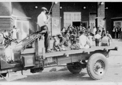 A black and white photograph. In the foreground is an open bed truck. In the bed, a man stands with a shotgun. An African-American man tends to the body of another, laid out on the bed.