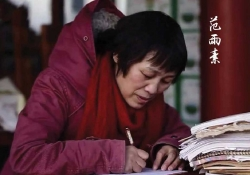 A photograph of a woman in a heavy red parka, hunched over a desk, writing