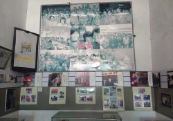 A wall of framed, aged photographs of female workers