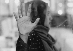 A black and white photograph of a woman, whose head is covered by a scarf, pressing her hand to a damp window between herself and the viewer. Her gaze is away from the viewer.