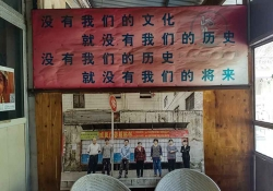 A photograph of several people standing in a row is mounted on a wall, beneath a banner adorned with Chinese characters