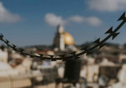 Jerusalem hangs out of focus in the background as a chain hangs across the image in the foreground