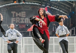 Three dancers on a large outdoor stage. Two male dancers, dressed in grey and black, flank a female dancer, dressed in black and red