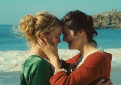 A still photograph from Portrait of a Lady on Fire that features two women standing on a beach, holding one another and pressing foreheads