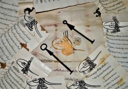 Pieces of paper, covered in Arabic writing, are scattered on a table. A pair of keys sits near the center