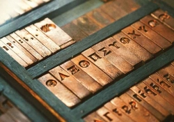 A photograph of Greek letters inscribed in typographical brass fonts