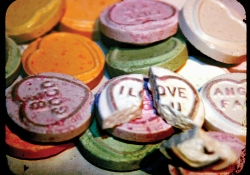 "A pile of conversation hearts with one that reads ""I Love You"" broken at the top of the pile"