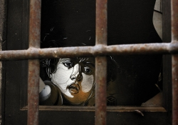 The drawn image of a human face peers from within a darkened room through iron bars