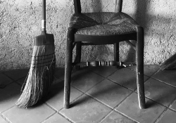 A black and white photograph of the bottom half of a broom and a chair against a rough-hewn wall