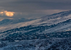 A photograph of a small village on a mountainside, shrouded in snow and shadow