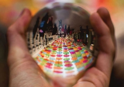 A polished steel ball held in a hand reflects a long table with colored plates on it