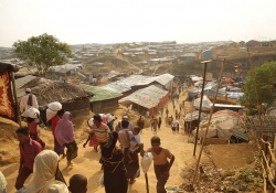 A photograph shot from a high vantage that shows refugees streaming in and out of the Kukupalong refugee camp