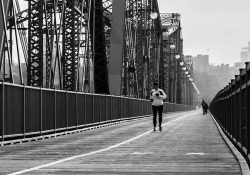 A black and white photograph of a person jogging toward the camera on a long suspension bridge
