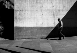 A black and white photo of a man walking down a sloping street in front of a wall transected by shadow
