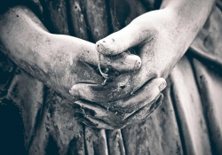 A somber black and white photo of the clasped hands of a statue, darkened by weathering