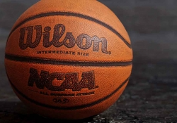 A close up photograph of a basketball. Text on the ball reads: Wilson. NCAA.