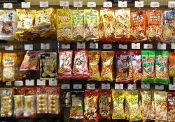 Packaged foods hang uniformly from wall pegs in a Japanese convenience store