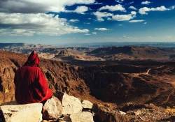 A photo of a figure, cloaked in red, sitting atop a mountain overlooking a wide vista below