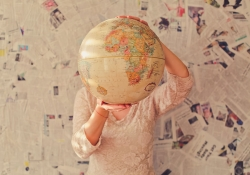 A woman stands in front of a wall covered in newspaper articles, holding up a tan colored globe that covers her face