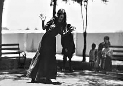 A grainy black and white photo of a woman in a long dress swaying at the waist with her hands up by her face