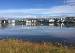 The city of Reykjavik framed in the foreground by a lake and in the background by cloud-capped mountains