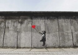 A painting of a girl in black and white holding a red balloon on a drab gray wall