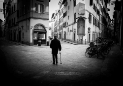 A black and white photo of a man using a cane staring at the buildings in an otherwise empty city