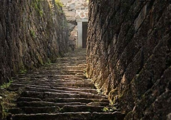 Steps, roughly cut from stone, leading steeply toward a door, partially obscured by the curvature of the rock