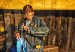 An older man in a hard hat and work coveralls appears as if he is speaking in a highly industrial location