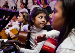 A young girl holding a guitar and surrounded by other children with instruments looks behind her