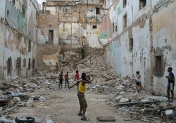 A group of boys play stickball in an urban cul-de-sac filling up with piles of rubble