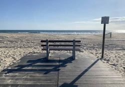 A photograph of an empty bench facing the ocean