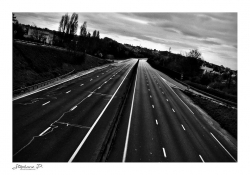 A black and white photograph of an deserted urban highway
