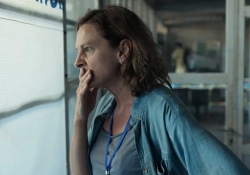 A photograph of a woman, her hand covering her mouth in a gesture of worry, stares out a window.