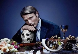 A promotional still of an actor, seated at a table, resting his chin atop his hand, which rests on a human skull