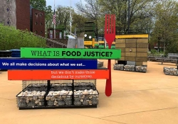 """A photograph of an outdoor art installation. In the foreground, an oversized fork stands besides signs that read, """"What is food justice? We all makes decisions about what we eat...but we don't make those decisions by ourselves."""""""