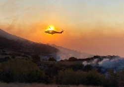A helicopter hovers above a smoldering, mountainous landscape. The sun is positioned just such that the helicopter appears to be on fire.