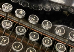 A close-up photograph of the punctuation/number row of a manual typewriter