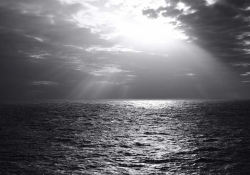 A black and white photograph of the sun peeking through the clouds above the ocean