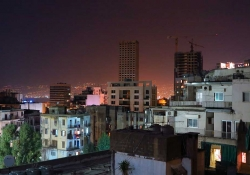 A photograph looking over the roof line at the city of Beirut at night