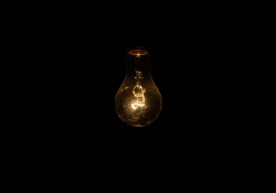 A photograph of a very dim lightbulb that is all but being swallowed by the darkness surrounding