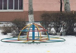 A photograph of a multi-colored merry go round on the snowy ground outside of a school