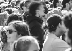 A black and white photo of a crowd with a figure at its center who is blurred