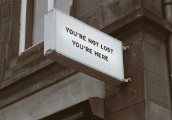 """A sign mounted on the corner of a building. The sign reads, """"You are not lost. You are here."""""""